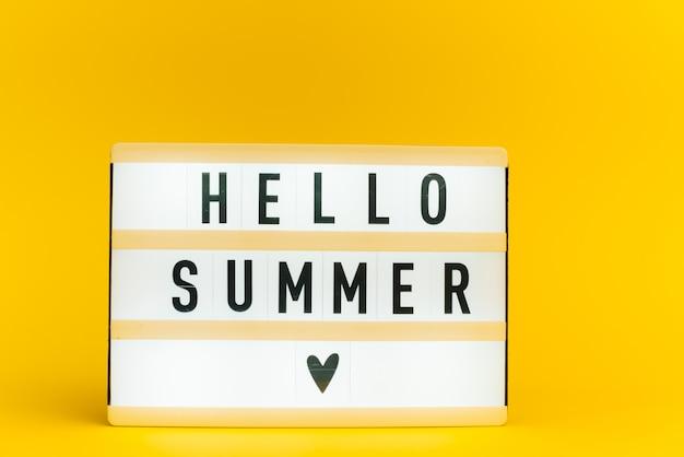 Scatola luminosa con testo, ciao estate, sulla parete gialla
