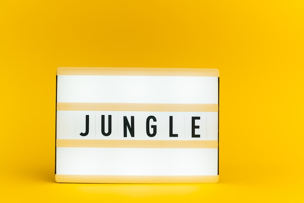 Scatola luminosa con testo, giungla, sulla parete gialla