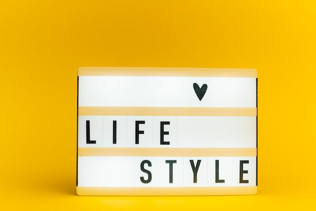 Scatola luminosa con testo, life style, sulla parete gialla