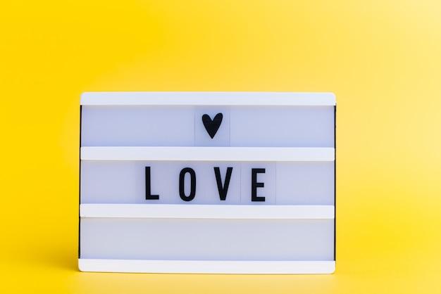 Scatola luminosa con testo, amore, sulla parete gialla