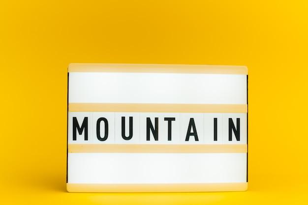 Scatola luminosa con testo, montagna, sulla parete gialla