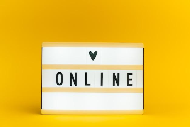 Scatola luminosa con testo, online, sulla parete gialla
