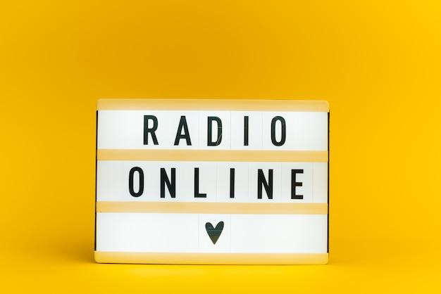 Scatola luminosa con testo, radio online, sulla parete gialla