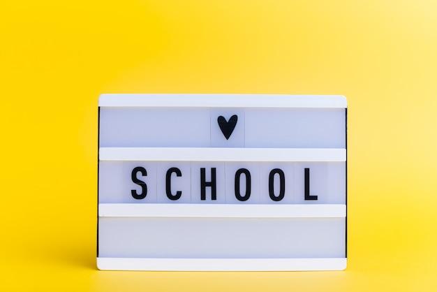 Scatola luminosa con testo, scuola, sulla parete gialla