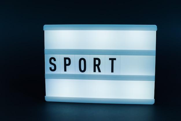 Scatola luminosa con testo, sport, su muro scuro