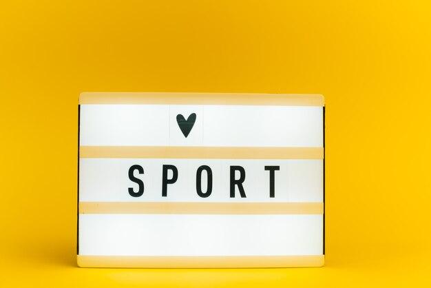 Scatola luminosa con testo, sport, sulla parete gialla