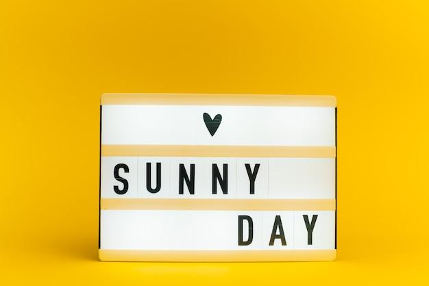 Scatola luminosa con testo, sunny day, sulla parete gialla