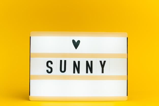 Scatola luminosa con testo, sunny, sulla parete gialla
