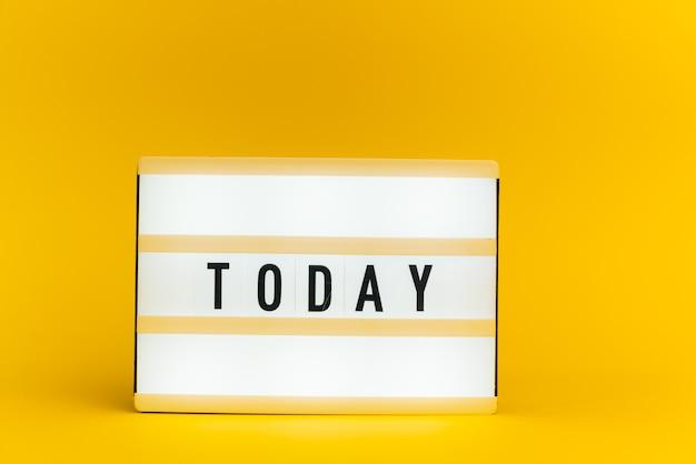 Scatola luminosa con testo, oggi, sulla parete gialla
