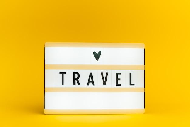Scatola luminosa con testo, viaggio, sulla parete gialla