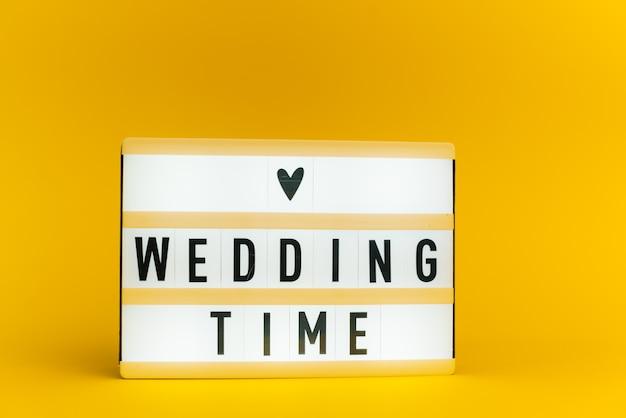 Scatola luminosa con testo, tempo di matrimonio, sulla parete gialla