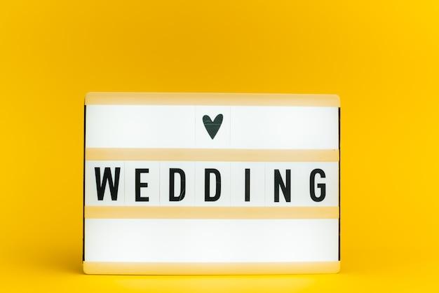 Scatola luminosa con testo, matrimonio, sulla parete gialla