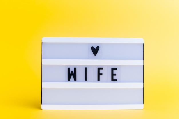 Scatola luminosa con testo, moglie, sul muro giallo