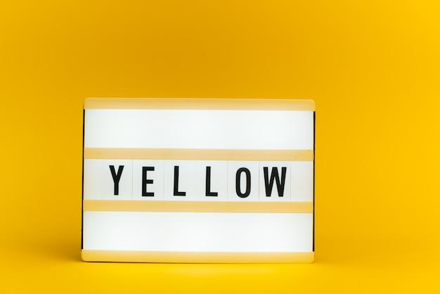 Scatola luminosa con testo, giallo, sulla parete gialla