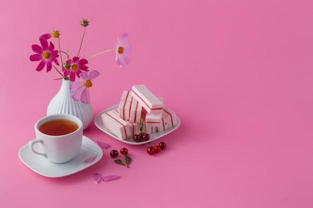 Colazione leggera o pranzo, ciliegia, frutti di bosco e tè nero su sfondo rosa