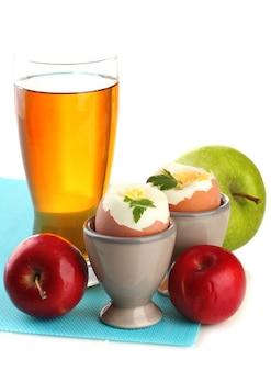 Colazione leggera con uova sode e bicchiere di succo, isolato su bianco