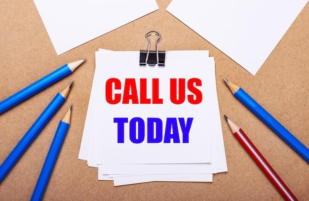 Su uno sfondo marrone chiaro, matite blu e rosse e carta bianca con il testo chiamaci oggi
