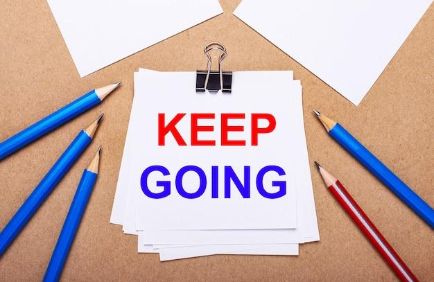 Su uno sfondo marrone chiaro, matite blu e rosse e carta bianca con il testo keep going