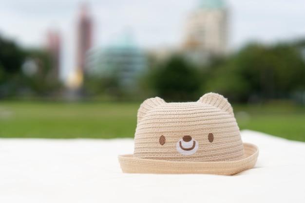 Cappello da orso bruno chiaro sul tappetino durante il picnic, nella giornata di sole con sfocatura del parco sullo sfondo della città.