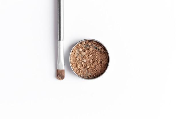 Ombretto marrone chiaro in contenitore e ombretto o pennello per il trucco. concetto di trucco laici piatta