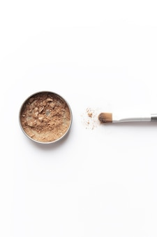 Ombretto marrone chiaro nel contenitore e ombretto o pennello per il trucco