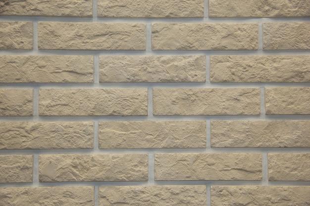 Muro esterno in mattoni di pietra marrone chiaro in luce dura che enfatizza le trame e la profondità della pietra.