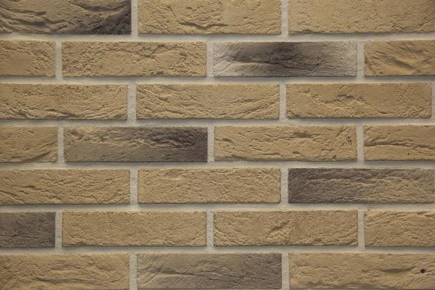 Muro esterno in mattoni di pietra marrone chiaro in luce dura che enfatizza le trame e la profondità delle pietre