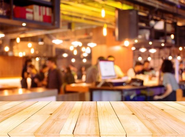Tavolo vuoto in legno marrone chiaro sul davanti con bar e ristorante sfocati sfocati.