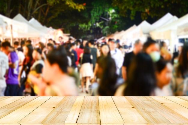 Tavolo in legno marrone chiaro sul davanti con sfocato sfocato folla di anonimi acquisti a piedi sul mercato notturno.