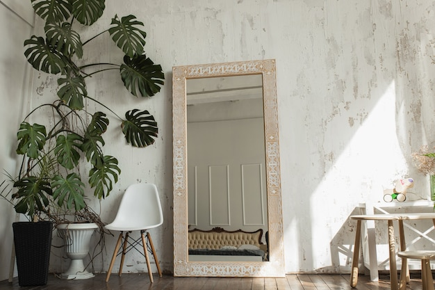 Specchio in legno marrone chiaro con motivi etnici in una stanza luminosa con pareti bianche