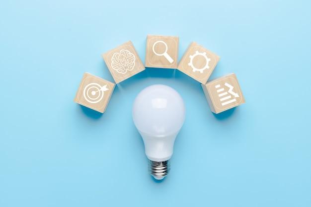 Lampadina su sfondo blu con icone di brainstorming e icona di fonti di business, innovazione e concetto creativo