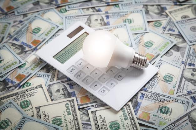 Lampadina e calcolatrice sulle banconote in dollari.