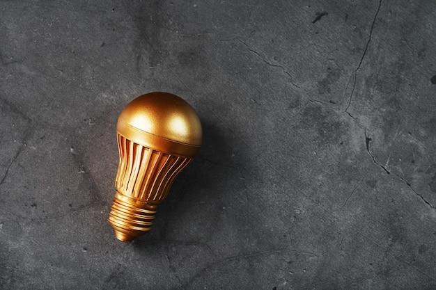 Lampadina da oro su pietra nera concetto di un'idea redditizia
