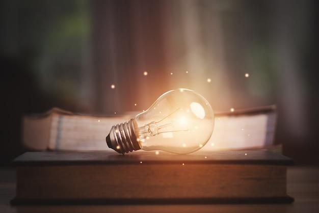 Lampadina incandescente sul libro. idea con innovazione e concetto di studio aziendale.