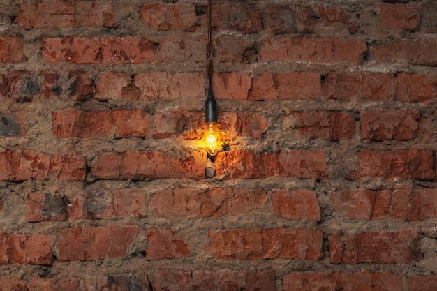 Lampadina appesa a un filo su un vecchio muro di mattoni
