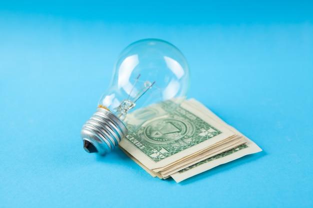 Lampadina e soldi sulla scena blu