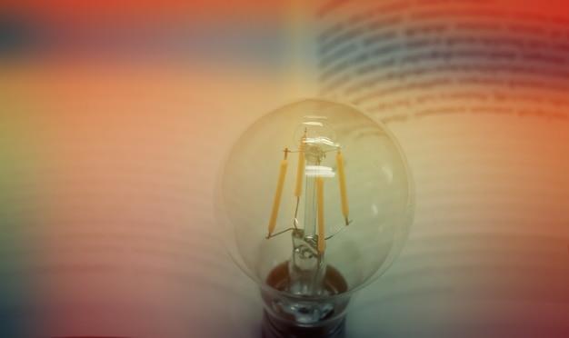 Lampadina con un concetto di idea di libro con innovazione