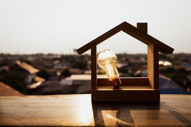 Lampadina con casa in legno sul tavolo