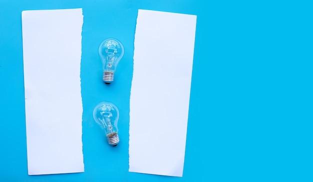 Lampadine con carta bianca sulla superficie blu