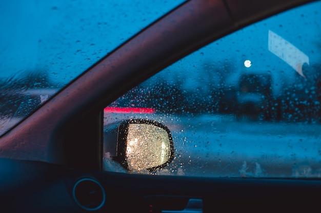 La luce dei fari dell'auto si riflette nello specchietto laterale dell'auto. mattina d'inverno di traffico automobilistico.