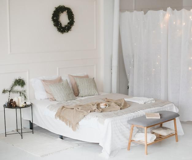 Camera da letto luminosa e accogliente decorata per natale e capodanno con una ghirlanda sul muro