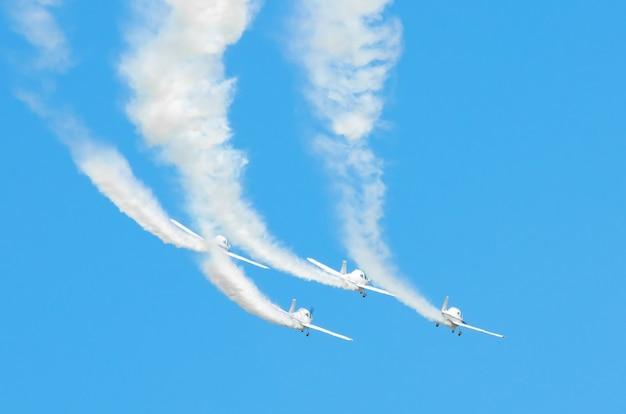 L'aeroplano a motore leggero con una traccia di fumo bianco vola in gruppi nel cielo azzurro con luce solare e abbagliamento.