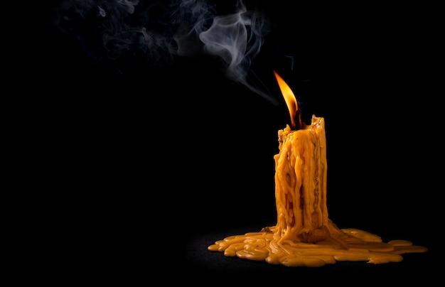 Candela della fiamma leggera che brucia brillantemente sul nero