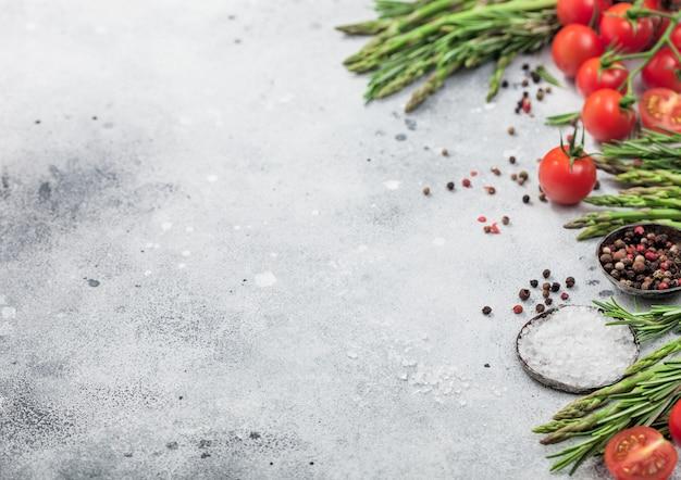 Sfondo di cibo leggero con pomodorini biologici sani, asparagi e rosmarino con una ciotola di pepe e sale. spazio per il testo