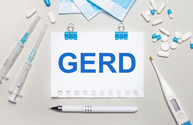 Su uno sfondo grigio chiaro, maschere mediche blu, siringhe, un termometro elettronico, pillole, una penna e un taccuino con la scritta gerd. concetto medico