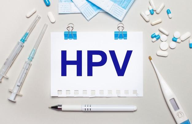 Su uno sfondo grigio chiaro, maschere mediche blu, siringhe, un termometro elettronico, pillole, una penna e un taccuino con la scritta hpv. concetto medico