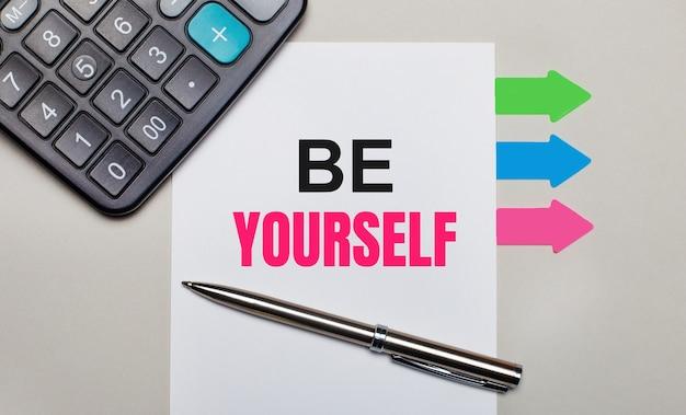 Su uno sfondo grigio chiaro, una calcolatrice, un foglio bianco con il testo be yourself, una penna e adesivi multicolori luminosi. vista dall'alto
