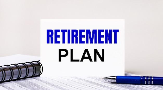 Su uno sfondo grigio chiaro, un taccuino, una penna blu e un foglio di carta con la scritta piano pensione. concetto di affari