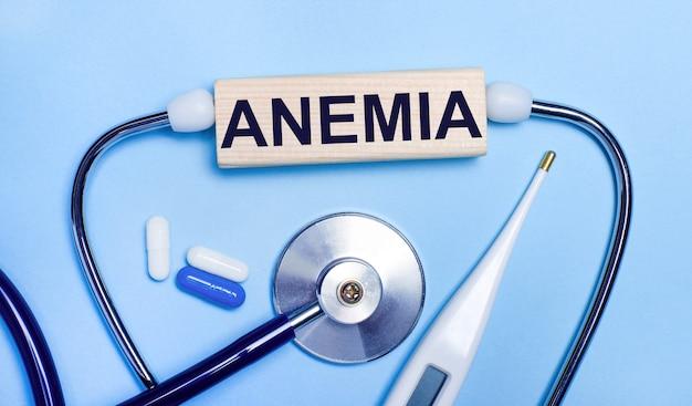 Su uno sfondo grigio chiaro, uno stetoscopio, un termometro elettronico, delle pillole, un blocco di legno con la scritta anemia. concetto medico.