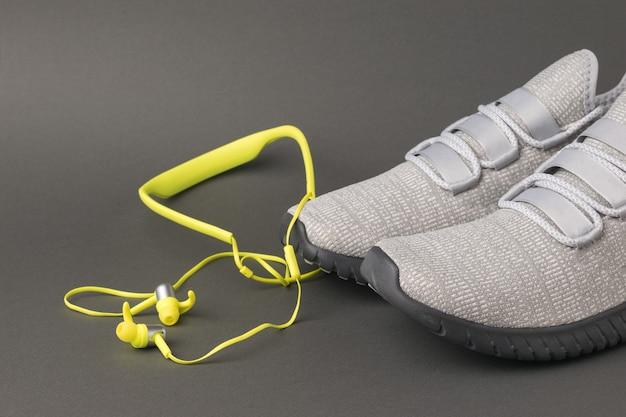 Scarpe da ginnastica grigio chiaro e cuffie gialle su sfondo grigio. stile di vita sportivo. colori 2021.